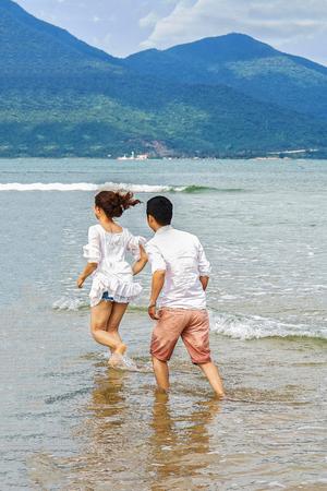 beachfront: Danang, Vietnam - February 20, 2016: Young couple running through the water in the China Beach in Danang, in Vietnam Stock Photo