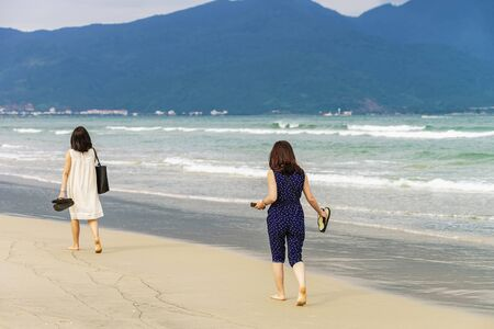 no face: Young girls passing by on the China Beach in Danang in Vietnam. No face Stock Photo