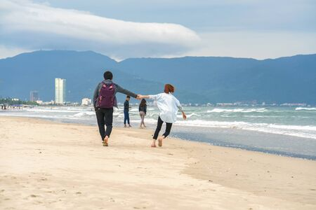 no face: Danang, Vietnam - February 20, 2016: Young couple passing by and holding hands at the China Beach in Danang, in Vietnam. No face