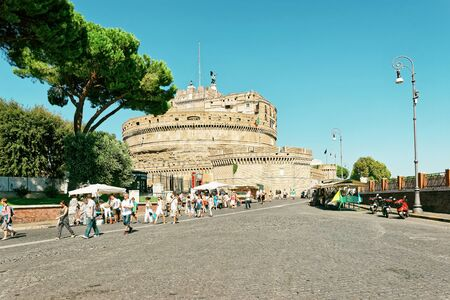 Rome, Italy - August 28, 2012: Castle of the Holy Angel, in Rome in Italy. It is is also called as Castel Sant Angelo. View from the bridge. Tourists in the street.