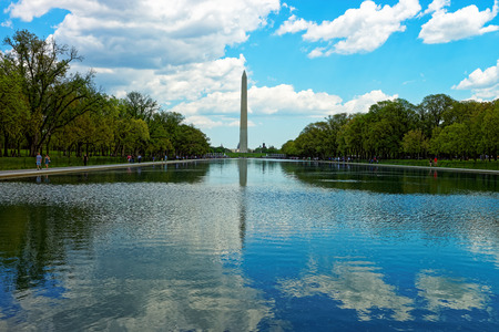 Monument of George Washington is reflecting in the water alongside the clouds. People are taking a walk during a beautiful day and enjoy the weather. Editorial