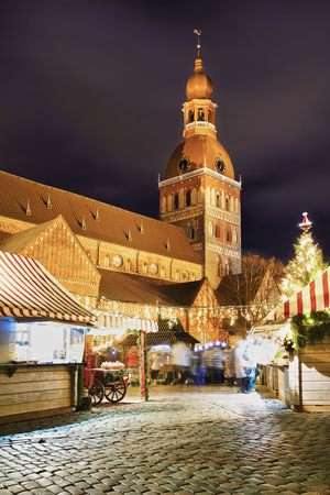 Christmas market at the Dome square near the Riga Cathedral in old Riga, Latvia. It is the oldest Medieval church in Baltic states. Motion blur. Selective focus