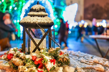 Christmas lantern pictured in front of the Christmas tree and market visitors in Vilnius, Lithuania. Each year, the capital hosts the Christmas Market where people can find various festive goods.
