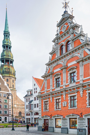 Riga, Latvia - December 26, 2015: Corner look at the House of the Blackheads and Saint Peter church in the old town of Riga, Latvia. Editorial