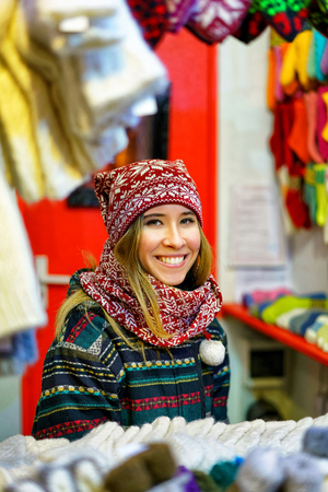 festively: Riga, Latvia - December 24, 2015: Young and festively dressed woman pictured while trading with various warm clothes at Riga Christmas Market. There people can find woolen socks, hats and gloves.