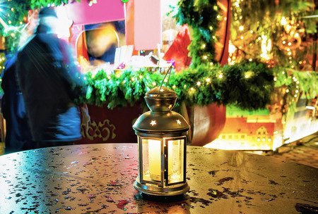 Bright lantern with the candle inside of it standing on one of the tables at the Christmas Market in Riga, Latvia. It is the symbol of cosiness and warmth during the celebrations.