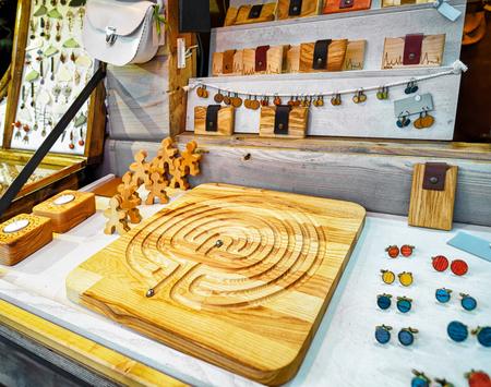 Riga, Latvia: One of the stalls with handmade leather and wooden souvenirs at the Christmas Market in Riga, Latvia. At this stall people can buy a handmade board game, cuff links