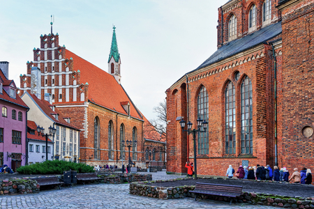 Riga, Latvia - December 26, 2015: People walking in the old town near the St John church in the center of Riga, Latvia. The church began from the small chapel which was originally built in 1234
