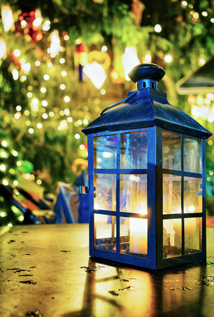 Festive lantern with the candle inside of it pictured on the table at the Riga Christmas Market in Latvia. It is one of the symbols of the celebration which shows the cosiness and warmth.