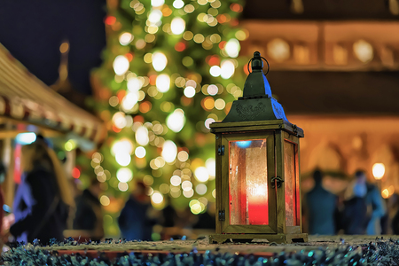 Glowing lantern with the candle inside photographed at the Christmas Market in Riga, Latvia. The market usually takes place from the late November till the beginning of January. Selective focus Stock Photo