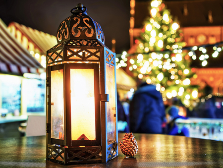 market place: Small cone near the glowing candle lantern on of the tables at the Christmas Market in Riga, Latvia. Market usually takes place from the late November till the start of January.
