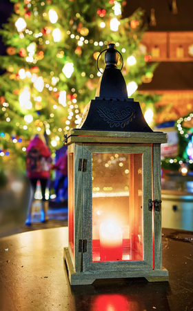 Glowing candle lantern representing cosiness at the Christmas Market in Riga, Latvia. At the market people can buy different festive goods, souvenirs, warm clothes and enjoy hot drinks and food. Stock Photo