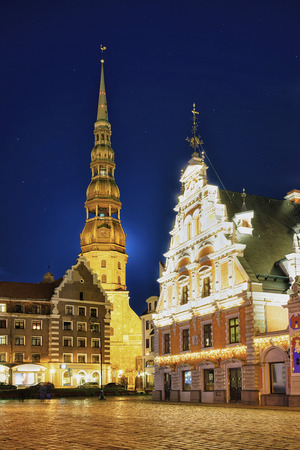 Night look at House of the Blackheads and Saint Peter church in Riga, Latvia. The House of the Blackheads was originally built in 14th century and the church was first mentioned in 1209.