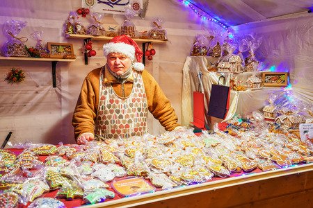 variously: Vilnius, Lithuania - December 27, 2015: Happy looking man selling the gingerbread goods at the Vilnius Christmas Market. Gingerbreads are variously decorated and mostly with different icing. Editorial