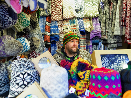 festively: Riga, Latvia - December 25, 2015: Festively dressed man selling woolen clothes at Riga Christmas Market. Warm mittens, gloves, socks and hats are one of the most common goods at the market.