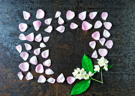 metallized: Frame of petals of pink tea rose and jasmine flowers on stone with metallized effect background. Flat lay.