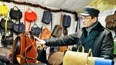 suggests: Vilnius, Lithuania - December 27, 2015: Man suggests customers handmade leather bags at the stall during Vilnius Christmas market. At the fair people can buy festive goods, souvenirs and warm clothes. Editorial