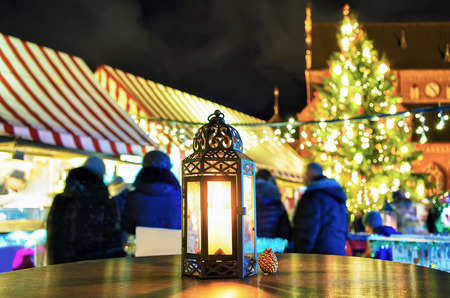christmas market: Small and bright lantern with the candle inside pictured at one of the tables at the Christmas Market in Riga, Latvia. People can find various festive goods, souvenirs, drinks and food at the market.