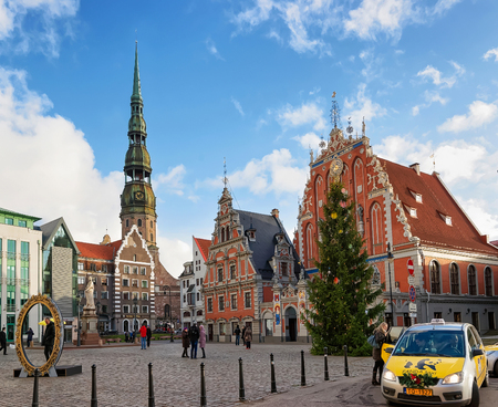 guild hall: Riga, Latvia - December 26, 2015: Taxi car and People near the House of the Blackheads and the Christmas tree near it during the Christmas season in Riga, Latvia Editorial