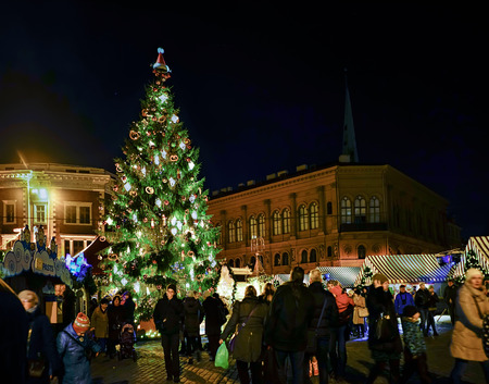 Riga, Latvia - December 24, 2015: People and Christmas tree at festive Christmas market. The Dome square in the center of old Riga, Latvia. At night