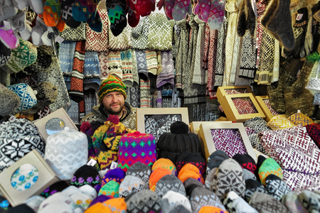festively: Riga, Latvia - December 25, 2015: Festively dressed smiling man selling woolen clothes at Riga Christmas Market. Warm mittens, gloves, socks and hats are one of the most common goods at the market.
