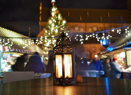 christmas market: Glowing candle lantern on the table at the Christmas Market in Riga, Latvia in the evening. Illuminated with light. Stock Photo
