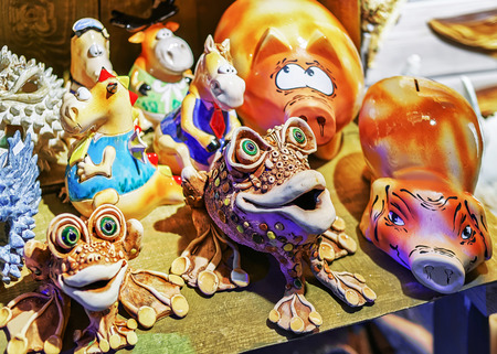 christmas frog: Riga, Latvia - December 26, 2015: Ceramic animal statues displayed for sale at the Christmas market in Riga, Latvia. At the fair people can find festive souvenirs, goods