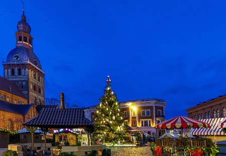 Glowing Christmas tree and market near the Riga Cathedral located at the Dome square in old Riga, Latvia. Dome cathedral was built near the river Daugava. Selective focus