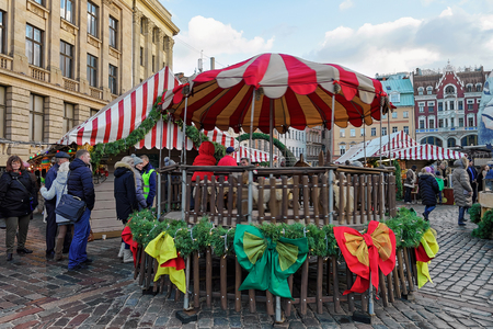 christmas bonus: Riga, Latvia - December 25, 2015: People at carousel at Christmas market on Cathedral square in old Riga. Selective bonus