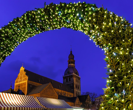 Entrance to the Christmas market and Riga Cathedral in the background at the Dome square in old Riga, Latvia. The Riga or Dome Cathedral was built in 1211 by Livonian Bishop Albert of Riga.
