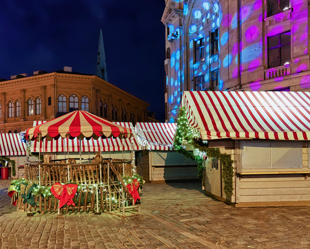 each year: Empty stands in the night at the Christmas market in old Riga, Latvia. The market takes place across the old town each year. Selective focus Stock Photo