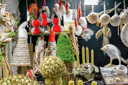 Golden tree, linen bird statue and other handmade souvenirs hanging for sale at the Christmas market in old Riga, Latvia. Selective focus Stock Photo