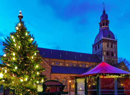 Glowing Christmas tree, Riga cathedral and market stalls at the Dome square in the center of the old Riga, Latvia. The Dome cathedral is the oldest church in Baltic states.