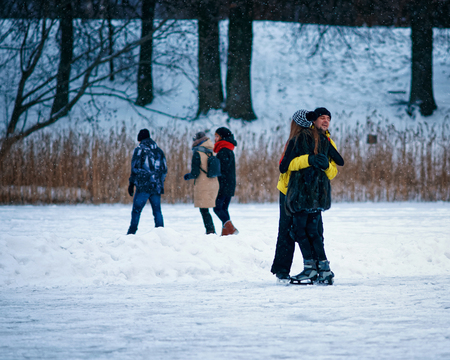 fellow: Young girl and fellow hug eath other at the winter rink covered with snow in Trakai, Lithuania.