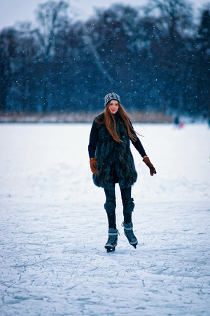 skating on thin ice: Young girl ice skating at the winter rink covered with snow in Trakai, in Lithuania.