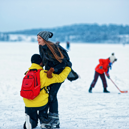 fellow: Young girl and fellow learn to ice skate at the winter rink covered with snow in Trakai, Lithuania. Stock Photo