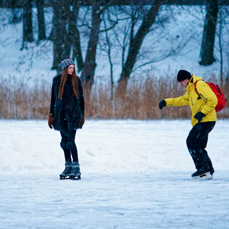 fellow: Young girl and fellow ice skating in the winter rink covered with snow in Trakai in Lithuania.