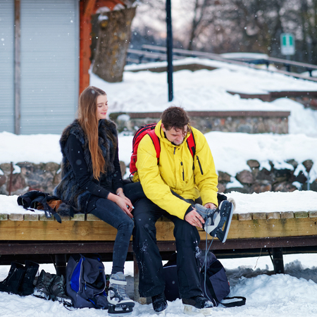 fellow: Young girl and fellow putting on skates and sitting on the bench in Trakai Lithuania. Stock Photo