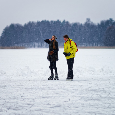 fellow: Young girl and fellow ice skating in the winter rink covered with snow in Trakai, Lithuania.
