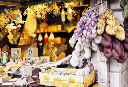 One of the stands with yarn and knitted souvenirs displayed for sale at the Christmas market in Riga, Latvia. At the fair people can also buy festive goods, warm clothes and traditional food. Stock Photo