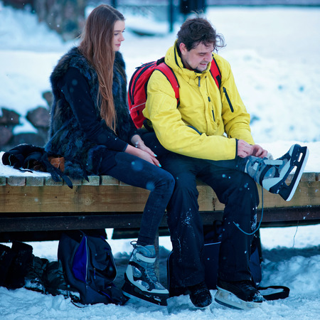 Young girl and fellow putting on skates and sitting on the bench in Trakai, in Lithuania. Stock Photo