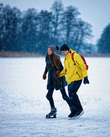 fellow: Young girl and fellow ice skating at the winter rink covered with snow in Trakai, in Lithuania. Stock Photo