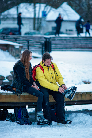 fellow: Young girl and fellow putting on skates and sitting on the bench in Trakai in Lithuania.
