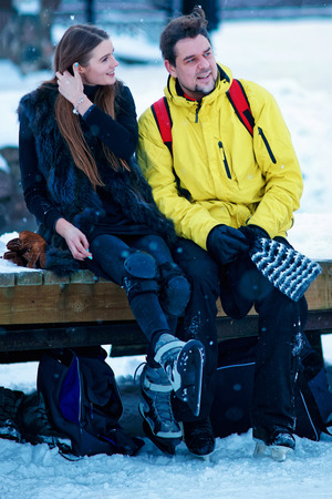 fellow: Young girl and fellow putting on skates and sitting on the bench in Trakai of Lithuania. Stock Photo