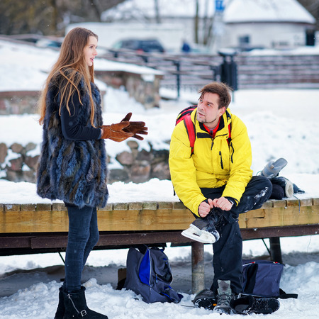 fellow: Young girl and fellow putting on skates and sitting on the bench in Trakai, of Lithuania.