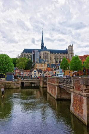 Amiens, France - May 9, 2012: Amiens Cathedral of Notre Dame and traditional houses on La place du Don Square at the embankment of Somme canal, Picardy, France. People on the background Editorial