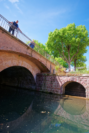 Colmar, France - May 1, 2012: Bridge in Little Venice quarter above River Auch in Colmar, Haut Rhin in Alsace, France. People on the background Editorial