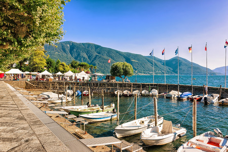 Ascona, Switzerland - August 23, 2016: Boats at the promenade of the luxurious resort in Ascona on Lake Maggiore in Ticino canton of Switzerland.