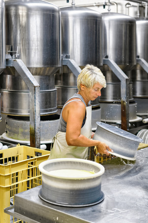 creamery: Evillers, France - August 31, 2016: Cheese-maker putting young Gruyere de Comte Cheese into the forms in the dairy in Franche Comte, Burgundy, France. Editorial
