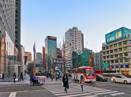 strret: Seoul, South Korea - March 11, 2016: City life with pedestrians crossing the strret, car traffic and Skyscrapers in Jung district in Seoul, South Korea